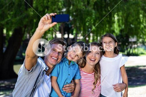 Happy family taking a selfie in the park