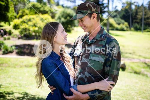 Happy soldier reunited with his partner in the park