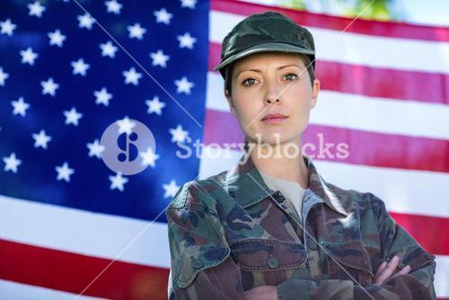 Soldier standing in front of american flag
