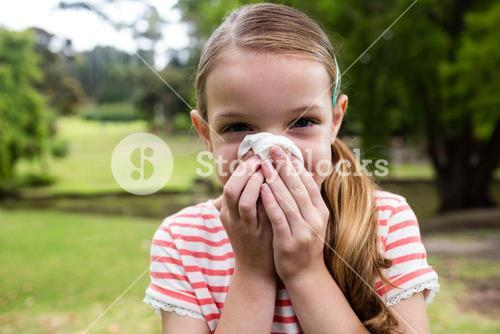 Sick girl sneezing in the park