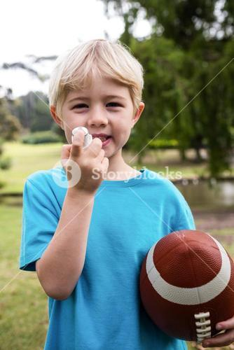 Boy with an american football using an asthma inhaler