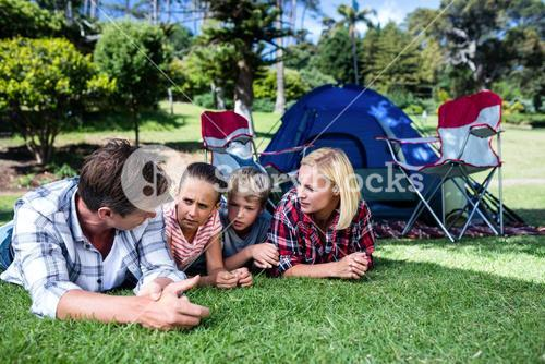 Family talking to each other while lying on grass