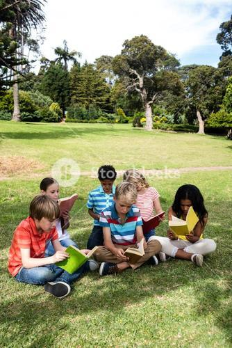 Children reading book in the park