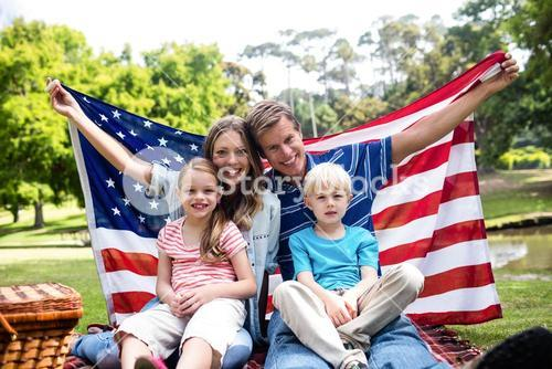 Hapy family holding american flag in the park