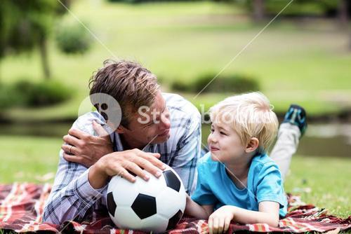 Father and son lying in the park