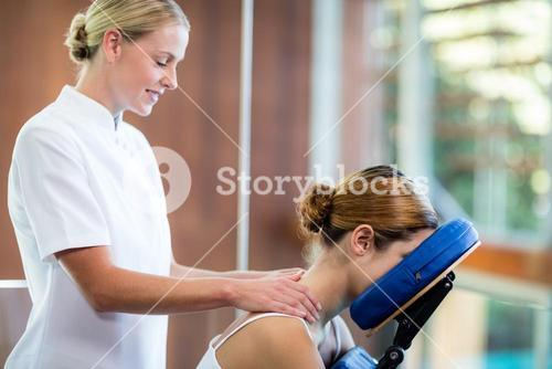 Woman receiving massage in massage chair
