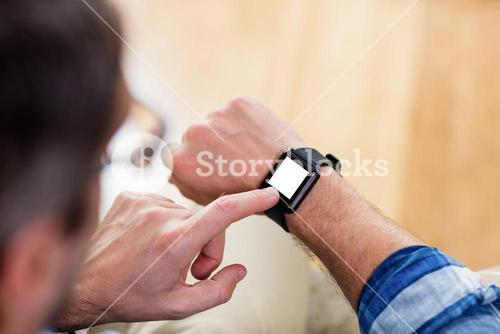 A man is touching his watch