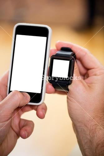 Mans hand holding a smart watch and a mobile phone