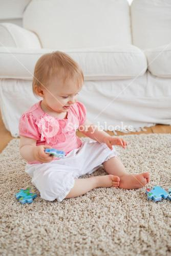 Baby playing with puzzle pieces while sitting on a carpet