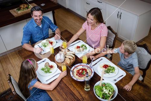 Happy family talking to each other while having meal in kitchen