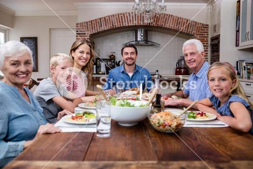 Multi-generation family having meal in kitchen
