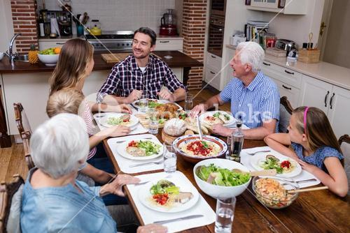 Multi-generation family talking while having meal in kitchen