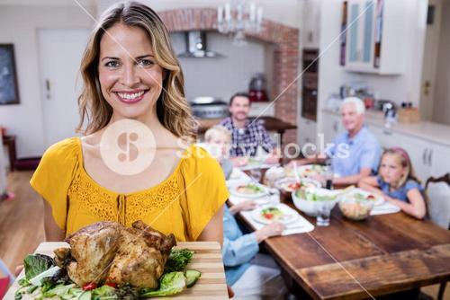 Portrait of happy woman holding a tray of roasted turkey