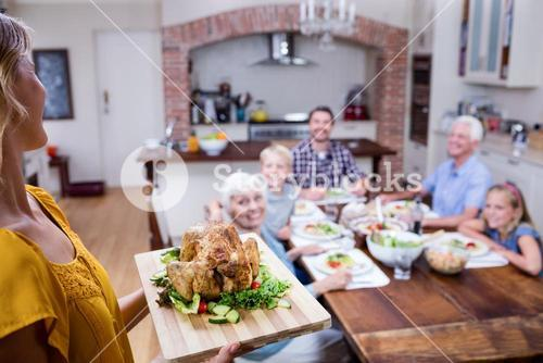 Woman holding a tray of roasted turkey