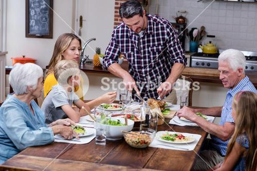 Man cutting roasted turkey while having meal with his family