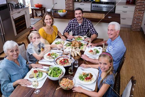 Portrait of multi-generation family having meal in kitchen