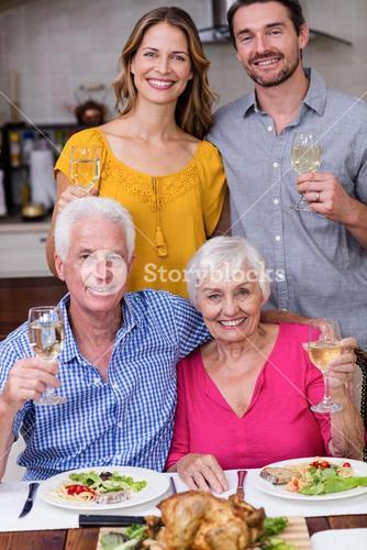 Portrait of a two generation family holding a wine glass at table