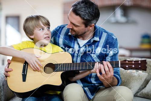 Father and son playing a guitar