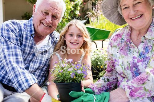 Portrait of grandparents and granddaughter holding flower pot