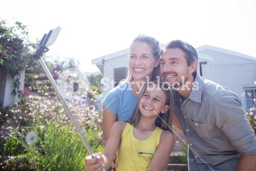 Parents and daughter taking a selfie with selfie stick