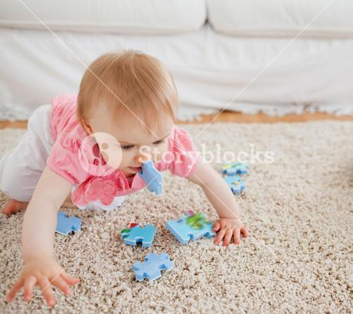 Lovely blond baby playing with puzzle pieces on a carpet