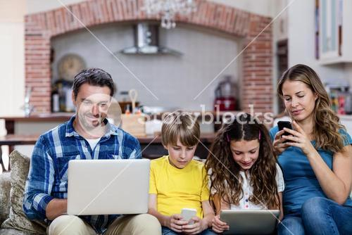Parents and kids using a laptop, tablet and phone