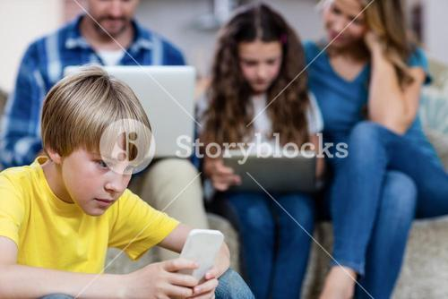 Boy using a mobile phone while family in background