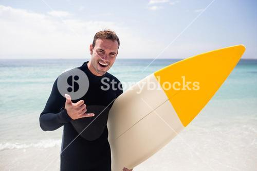 Surfer with surfboard gesturing hand sign on beach
