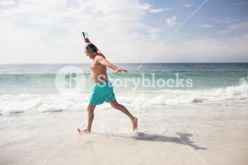 Senior man dancing on beach