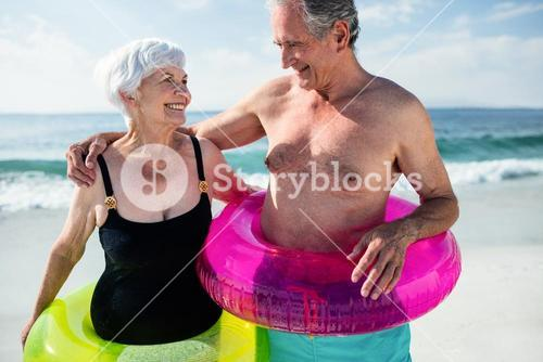 Senior couple in inflatable ring standing on beach