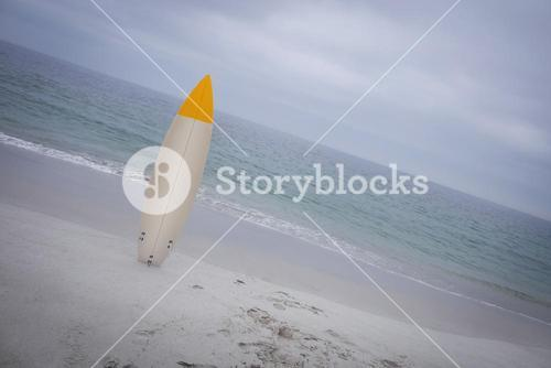 Surfboard standing on sand