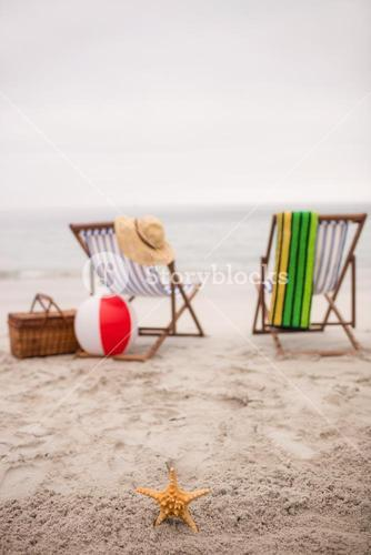 Empty deck chairs and star fish on the beach