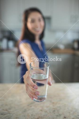 Young woman holding a glass of water in kitchen