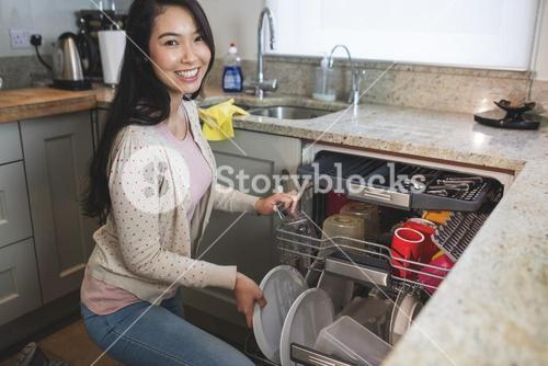 Portrait of woman arranging plates in dish washer