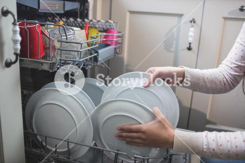 Woman arranging plates in dish washer