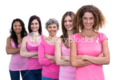 Smiling women in pink outfits standing in a line for breast cancer awareness