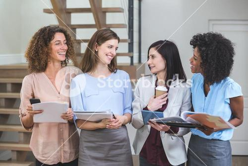 Female business colleagues standing together with file and digital tablet