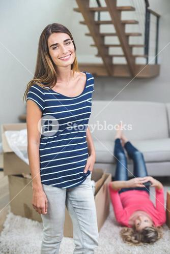 Portrait of beautiful woman standing in living room with hands in pocket