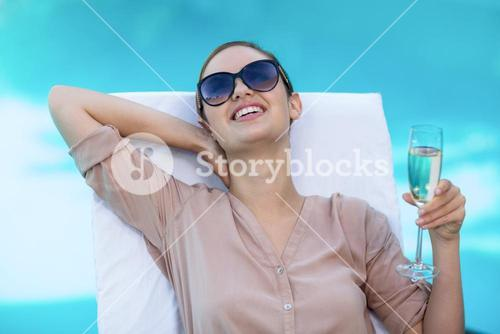 Business woman with a glass of champagne relaxing on sun lounger