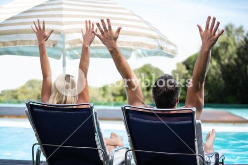Rear view of couple relaxing on sun lounger with hand raised