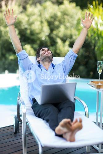 Excited man using a laptop near pool