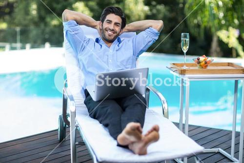 Smart man with a laptop relaxing on sun lounger