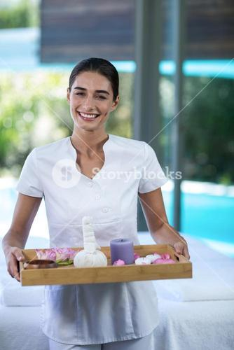 Female masseur holding a tray with spa therapy products