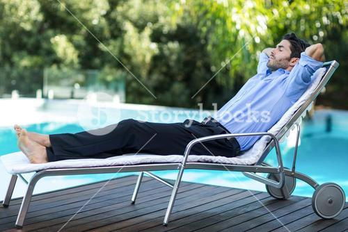 Smart man relaxing on sunlounger