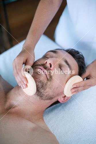 Man receiving a facial massage from masseur