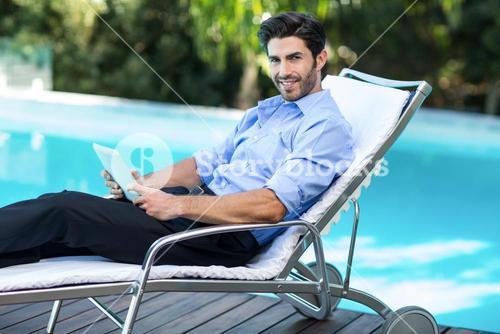 Smart man using digital tablet near pool