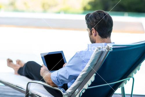 Man using digital tablet near pool