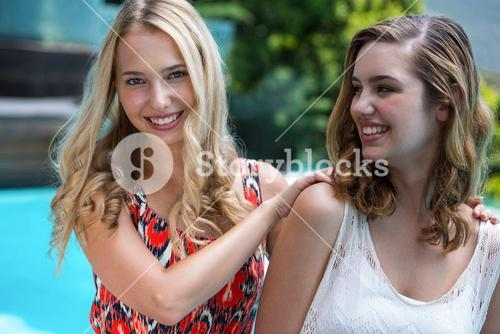 Beautiful women smiling near pool