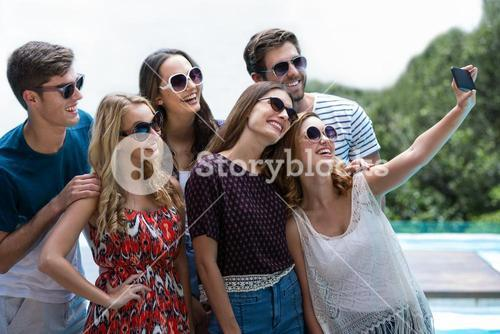 Happy friends taking a selfie near swimming pool