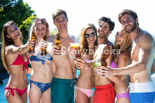 Group of happy friends showing beer bottles and glass of cocktail